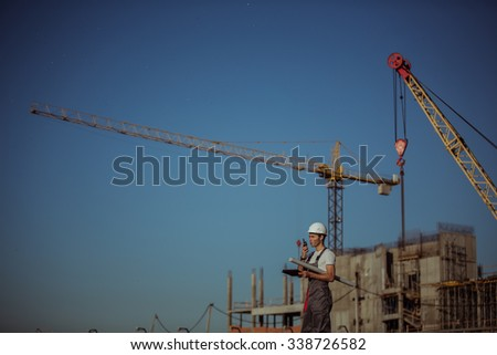 Engineer builder using tablet and walkie talkie, giving instructions at a construction site - stock photo