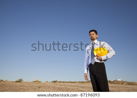 Engineer Businessman at the field holding a hardhat