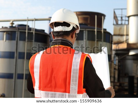 engineer checking a drawing on location - stock photo