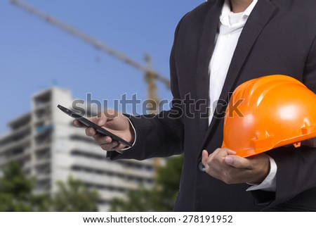 engineer checking emails on the phone on construction background - stock photo