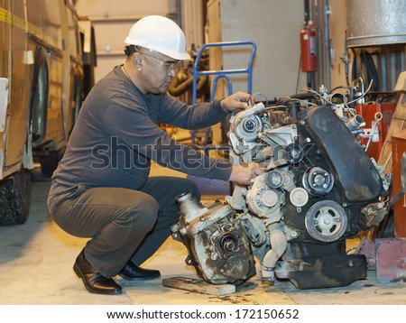 engineer checks the automobile mechanism in garage - stock photo