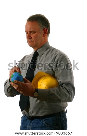 Engineer examining the earth with neutral expression on his face - stock photo