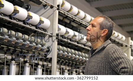 Engineer Examining Thread in Textile Mill. Portrait of an engineer in front of automated machines for Yarn manufacturing. - stock photo
