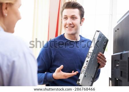 Engineer Giving Advice On Installing Digital TV Equipment - stock photo