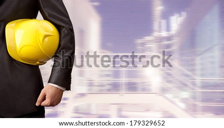 engineer hand and torso holding yellow helmet for workers security on the background of a new high-rise apartment buildings evening dark sky Well dressed Business man in black suit and white shirt - stock photo