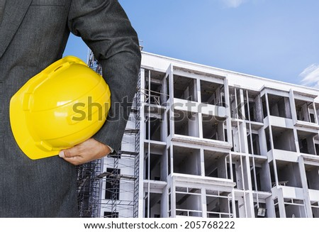 Engineer hand holding yellow helmet against the background of building under construction