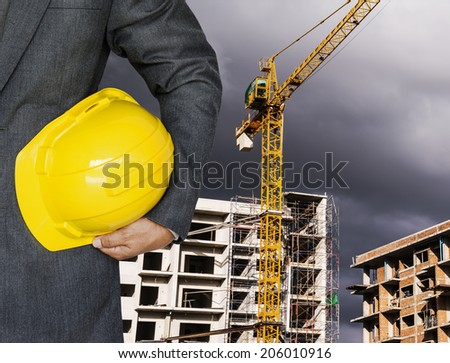 Engineer hand holding yellow helmet against the background of building under construction on dark clouds before raining