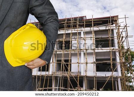 Engineer hand holding yellow helmet for workers security against the background of building under construction