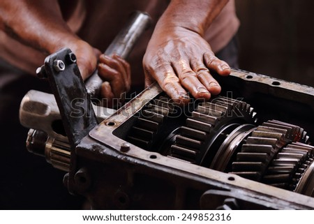 Engineer hands fixing engine power transmission gears box - stock photo