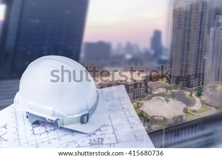 engineer helmet with plan for construction and blur city building background - stock photo