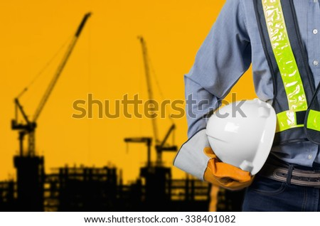 Engineer holding a white helmet for the safety of construction workers on a background crane Silhouette sunset. - stock photo