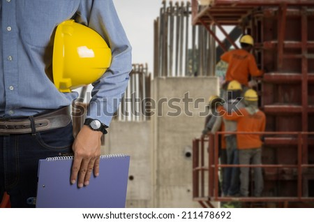 Engineer holding a yellow helmet for the safety of workers on a background of building new apartments and construction workers. - stock photo
