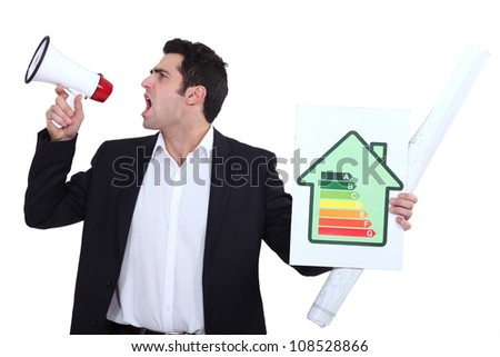 Engineer holding an energy efficiency rating sign and yelling into a blowhorn - stock photo