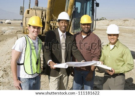 Engineer holding blueprint at construction site - stock photo