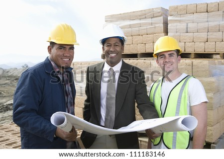 Engineer holding blueprint to workers at construction site
