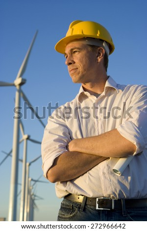 Engineer Holding Blueprints in Front of Modern Wind Turbines - stock photo