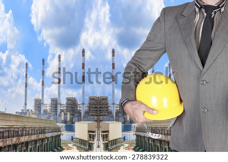 Engineer holding hard hat for working at Industrial power plant with cloud sky - stock photo