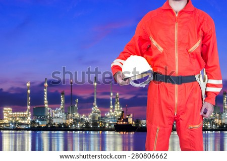 Engineer holding hard hat for working at oil refinery petrochemical industrial plant at twilight - stock photo