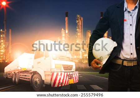 engineer holding hard hat standing against beautiful lighting of oil refinery in heavy petrochemical industry and big oil container truck use for petroleum industrial and land transport business - stock photo