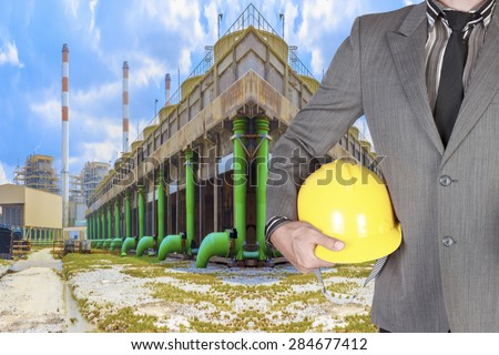 Engineer holding hard hat working at cooling tower of Industrial power plant  - stock photo