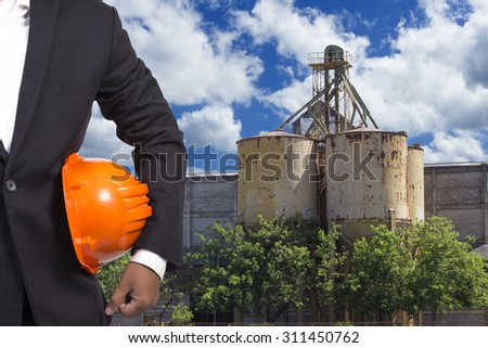 engineer holding helmet working at high building construction site against blue sky with in concept ecology and real estate - stock photo