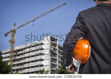 engineer holding orange helmet for workers security on construction background