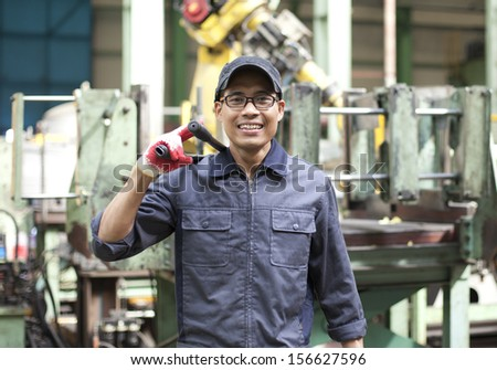 Engineer holding tool work with robot machine in background - stock photo