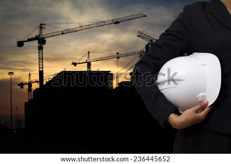 engineer holding white helmet for workers security on background of building construction - stock photo