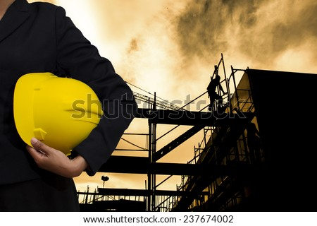 engineer holding Yellow helmet for workers security on background of building construction - stock photo