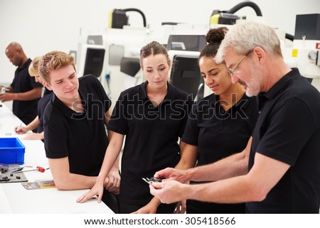 Engineer In Factory With Apprentices Checking Components - stock photo