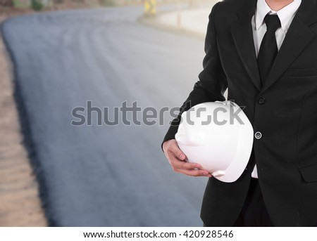 engineer in suit holding helmet with asphalt road under construction background - stock photo