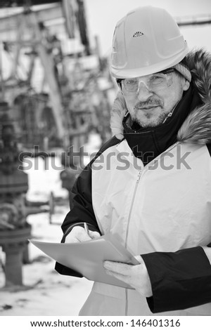 Engineer in uniform and helmet on of background the pump jack. Black and white. - stock photo