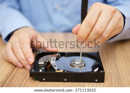 Engineer is recovering data from failed hard disk drive - stock photo