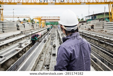 Engineer looking at Casting Plant Stake over Blurred construction worker on construction site - stock photo