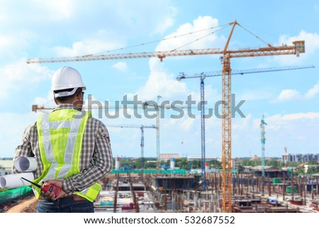 Engineer looking at large building construction site
