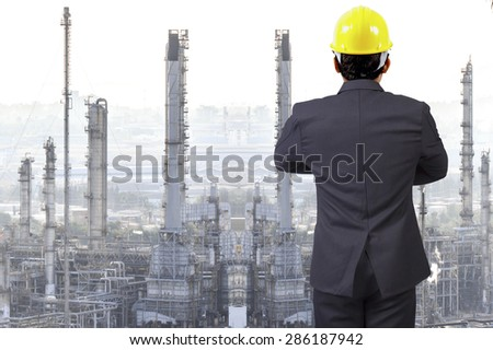 Engineer looking at oil refinery petrochemical industrial plant - stock photo