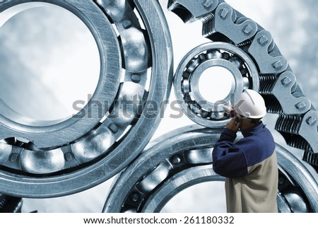 engineer, mechanic pointing at giant ball-bearings powered by chain,  - stock photo