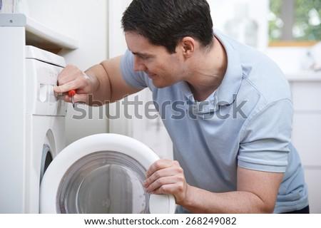 Engineer Mending Domestic Washing Machine - stock photo