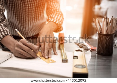 Engineer of architect starting draw a house blueprint on the desk in the office at construction working site, hipster view photography with sunlight effect vintage tone.