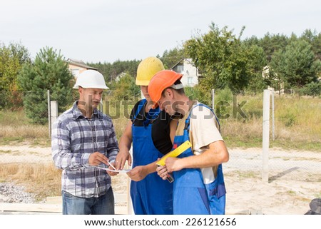 Engineer on a construction site discussing specifications with two workmen in overalls and hardhats as they group together around a document - stock photo