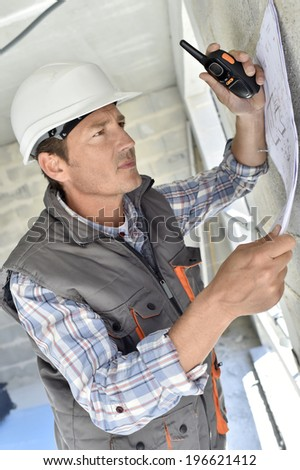 Engineer on building site checking blueprint