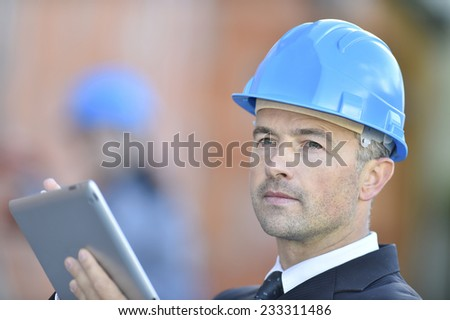 Engineer on building site using digital tablet - stock photo
