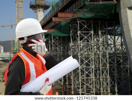 Engineer on construction site using mobile cellphone