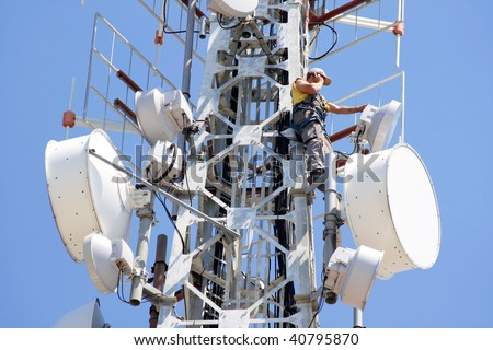 Engineer on phone on top of telecom pylon - stock photo