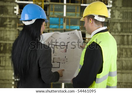 Engineer on the site showing to the buyer what the project, both with protective helmet - stock photo