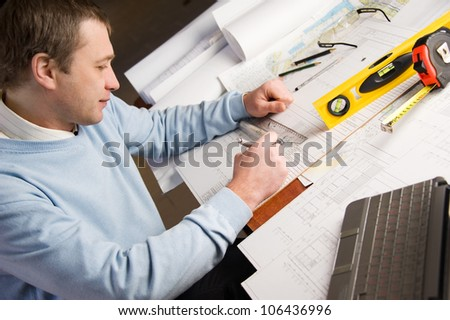 Engineer or architect in blue pullover is working on construction plans. - stock photo