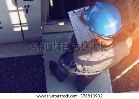 engineer or electrician working on checking status step up transformer high voltage on transformer yard and solution problem to operate at green energy solar power plant