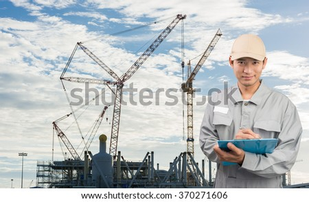 Engineer or technician write book with buildings and construction cranes on background