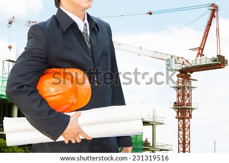 engineer orange helmet for workers security on the background of a new high-rise apartment buildings and construction cranes - stock photo