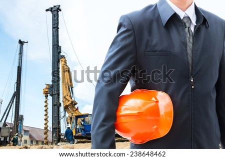 engineer orange helmet for workers security over new houses and crane background  - stock photo